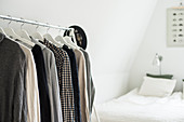 Clothing on hangers on clothes rail in bedroom