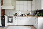 Small log burner in kitchen in Scandinavian country-house style