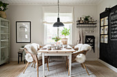 Fur rugs on wicker chairs around set table in dining room with chalkboard wall
