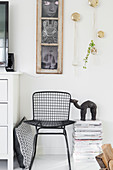 Black metal chair and stacked magazines below old window used as picture frame