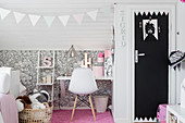 Fitted wardrobe with black door in child's bedroom with sloping ceiling