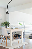 Shell chairs around white dining table next to balustrade of gallery above living space