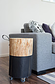 Tree trunk half painted black on castors and with loop handle used as side table