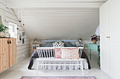 Spoke-back bench at foot of bed with valance below sloping ceiling in bedroom