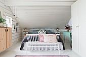 Sprossenbank vorm Bett mit Volant unter der Schräge im Schlafzimmer