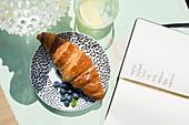 Teller mit Croissant und Blaubeeren neben aufgeschlagenem Notizbuch