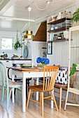 Spoke-back bench and various chairs around table in kitchen-dining room