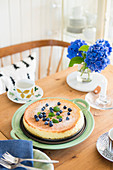 Cake with blueberries and vase of hydrangeas on set table