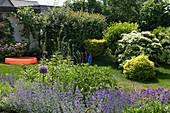 House garden with paddling pool, blue shrub bed