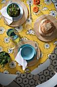 Gedeckter Tisch mit gelber Tischdecke im Retrodesing