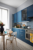 Round dining table and blue kitchen cabinets in kitchen-dining room