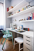 Upholstered chair and stool below desk resting on drawer units