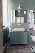 Oval countertop sink on blue base unit in bathroom
