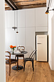 White retro fridge in niche in floor-to-ceiling fitted cupboards