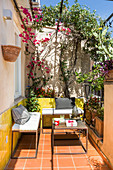 Small balcony with yellow wall tiles, boxy iron furniture and climber-covered pergola