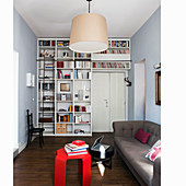 Sofa and floor-to-ceiling fitted shelves next to and above doorway in small apartment