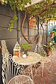Romantic, metal garden furniture against wall below pergola