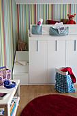 Hochbett in Kinderzimmer mit Treppenaufgang und Stauraum-Schränken