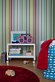 Side table with shelf on castors against multicoloured striped wallpaper in sibling's bedroom