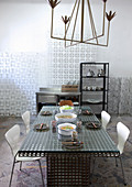Iron, brass-effect designer chandelier above iron mesh table in artist's studio apartment