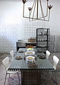 Design-Eisenkronleuchter in Messingoptik über Eisen-Fachwerktisch in Künstleratelier-Wohnung