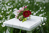 Small bouquet with apple blossoms, parrot tulips and red daisies on a side table in the meadow