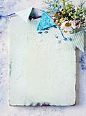 Weiss gestrichenes Holzbrett mit Wimpelkette und Wiesenblumenstrauss