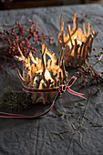 Wintry candle lanterns made from pieces of weathered wood and ribbons