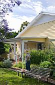 Gelb-weißes Holzhaus mit überdachter Veranda und sommerlichem Garten