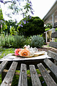 Romantic roses on tray on wooden table next to weathered wooden bench in garden