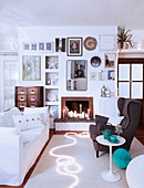 Sofa and wing-back chair in front of fireplace in festively decorated white living room
