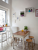 Seating area in window and antique stools around vintage wooden table in small bistro