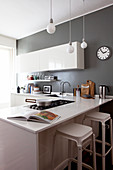 Glossy white cabinets in kitchen with grey walls