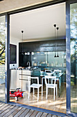 View from wooden terrace through open terrace doors into kitchen with steel counter and dining table
