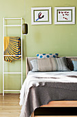 Metal ladder used as rack next to wooden bed against pastel green wall