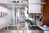 Blick über Edelstahl-Kücheninsel durch Glaswände in Wohnbereich mit Sofa und Schrankwand