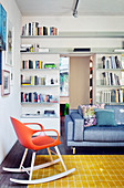 Couch and designer rocking chair in interior with floor-to-ceiling bookshelves
