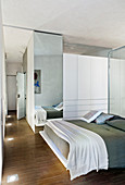 Open-plan bedroom with glass partition as headboard and floor-to-ceiling mirror