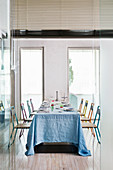 Long dining table set for 8 with blue tablecloth and colourful steel-tube chairs