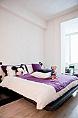 Double bed with purple and white bed linen in modern, open-plan bedroom
