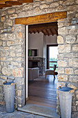 View through open door into Tuscan country house with stone walls