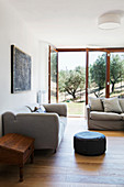 Grey sofas in living room and view of Tuscan countryside through open terrace doors