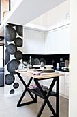 Moderne schwarz-weiße Küche hinter Abtrennung in Loft-Wohnung