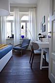 Blick in weiß-blau gestaltetes Schlafzimmer einer Altbauwohnung