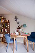 Runder Kaffeetisch mit blauen Stühlen in weihnachtlich dekoriertem Raum unter Dachschräge