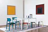 Two blue-painted chairs and several colourful stools around table