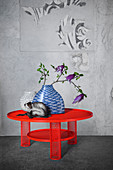 White glass vase, blue ceramic vase with fish pattern and china monkey on red steel mesh table