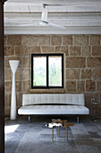 White, modern sofa and designer standard lamp against rustic stone wall
