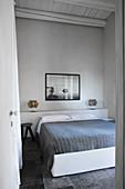 Schlicht gehaltenes Schlafzimmer in Grau- und Weißtönen mit Doppelbett und Wandbild