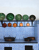 Antique ceramic bowls and old copper pans in country-house kitchen with blue and white tiled surfaces